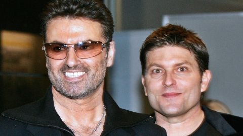 """George Michael, left, with his partner Kenny Goss at a reception after the Japan premiere of his autobiographical movie """"George Michael: A Different Story,"""" in December 2005. In 1998, Michael told CNN in an exclusive interview that he was gay."""