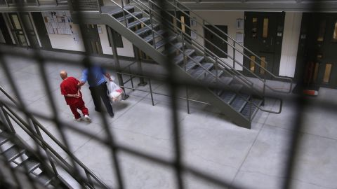 A guard escorts an immigrant detainee at the Adelanto Detention Facility in 2013.