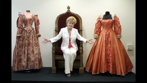 """Reynolds poses before the auction of her massive collection of memorabilia from classic movies in 2011. Reynolds is siting on the throne from the 1955 movie """"Virgin Queen"""" with a dress worn by Bette Davis, right,  and Joan Collins, left."""