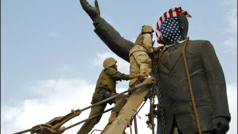 IRAQ - APRIL 09:  Operation Iraqi Freedom - Day 21: Us Troops Enter Central Baghdad And Topple Statue Of Saddam Hussein On April 9, 2003 In Baghdad, Iraq. Members Of The Us Marine 3Rd Battalion 4Th Regiment Share In The Celebration With Iraqis. Liberated By U.S. Led Troops, Thousands Of Jubilant Iraqis Celebrated The Collapse Of Saddam Hussein Murderous Regime, Beheading A Toppled Statue Of Their Longtime Ruler In The Center Of Baghdad And Looting Government Sites.  (Photo by Gilles BASSIGNAC/Gamma-Rapho via Getty Images)