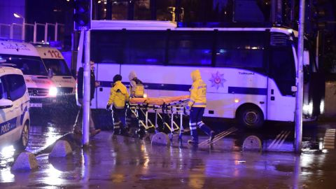 Medics wheel a stretcher at the scene.