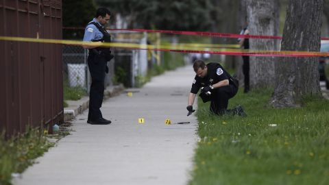 CHICAGO, IL - APRIL 25: A Chicago Police officer, left, watches as a evidence technician officer investigates a gun at the scene where a 16-year-old boy was shot in the head and killed and another 18-year-old man was shot and wounded on the 7300 block of South Sangamon Street on April 25, 2016 in Chicago, Illinois. Last week Chicago reached over 1,000 people shot since the beginning of the year. (Photo by Joshua Lott/Getty Images)