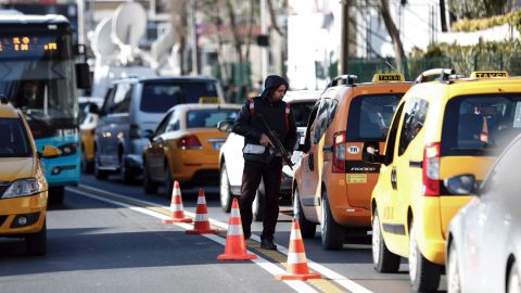 A police officer inspects cars near the scene on January 2.