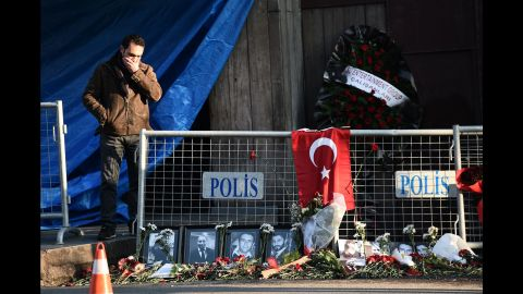 A friend of someone killed in the attack reacts near victims' pictures outside the nightclub on January 2.