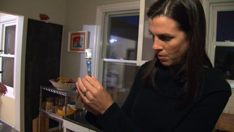 A woman is preparing a needle of insulin