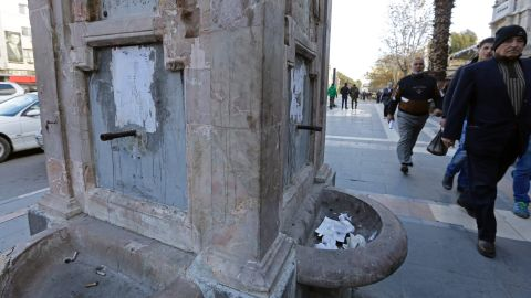 Residents walk past a drinking fountain that has run dry.