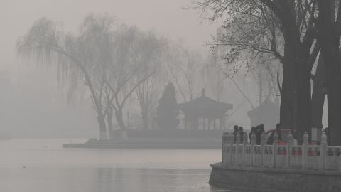 Visitors walk beside a lake on a heavily polluted day in Beijing on January 1, 2017. China's capital city started the year under a heavy blanket of grey smog, with a concentration of toxic particles 20 times higher than the maximal level recommended by the World Health Organization, as a new pollution cloud was - again - striking the country. / AFP / GREG BAKER        (Photo credit should read GREG BAKER/AFP/Getty Images)