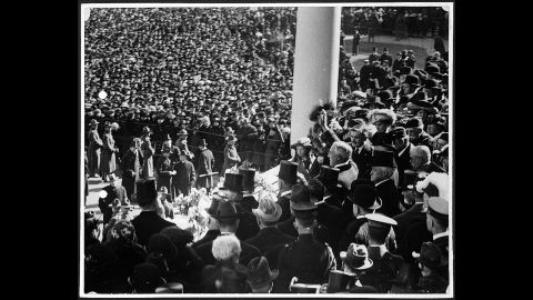 President Warren G. Harding waves to the crowd from the US Capitol's east portico in 1921. It was the first inauguration where an automobile was used to transport the president-elect to the Capitol.