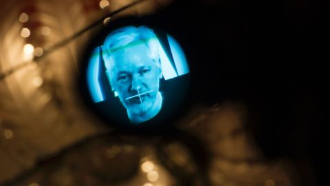 Julian Assange, founder of the online leaking platform WikiLeaks, is seen through the eyepeace of a camera as he is displayed on a screen via a live video connection during a press conference on the platform's 10th anniversary on October 4, 2016 in Berlin.
