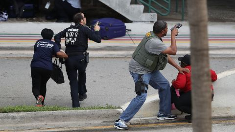 Police assist people seeking cover outside Terminal 2 at the Fort Lauderdale airport.