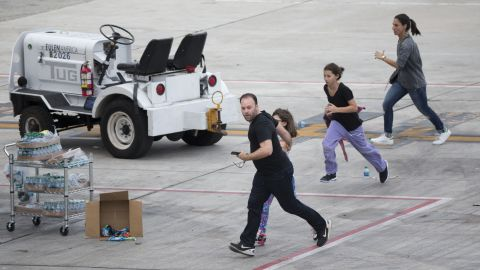 """People run out on the tarmac in the aftermath of the shooting Friday, January 6, at the airport in Fort Lauderdale, Florida. <a href=""""http://www.cnn.com/2017/01/06/us/fort-lauderdale-airport-incident/index.html"""" target=""""_blank"""">Five people were killed and eight others were wounded</a>, officials said."""
