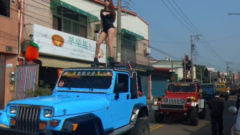 This picture taken on January 3, 2017 shows pole dancers performing on top of jeeps during the funeral procession of former Chiayi City county council speaker Tung Hsiang in Chiayi City, southern Taiwan. Fifty pole dancers clad in black bikinis gave one Taiwan politician a raucous final send-off in an eyebrow-raising funeral parade that jammed traffic and drew crowds of onlookers.  / AFP / STR / Taiwan OUT        (Photo credit should read STR/AFP/Getty Images)