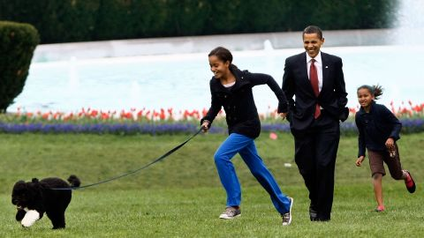 """The President takes Malia, left, and Sasha for a walk <a href=""""http://www.cnn.com/2009/POLITICS/04/14/first.dog/"""">with their new dog, Bo,</a> on the South Lawn of the White House in April 2009. The Portuguese water dog was a gift from Sen. Edward Kennedy. The first family chose the purebreed puppy largely because of Malia's allergies."""