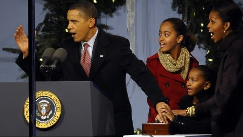 With an assist from his wife and daughters, Obama presses the button to light the National Christmas Tree on December 2009 at the Ellipse near the White House.