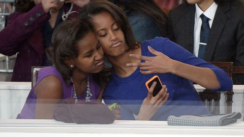 The first daughters take a selfie of themselves during the presidential inaugural parade on January 21, 2013, in Washington. Malia was 14 and Sasha 11 at the time of their father's second inaugural.