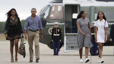 Obama and the first lady head to the tarmac to board Air Force One with their daughters Malia, right, and Sasha, left, at Air Station Cape Cod in Massachusetts in August 2016.
