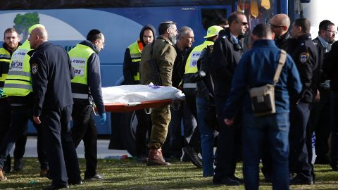 Israeli medics carry a covered body from the scene of the attack.