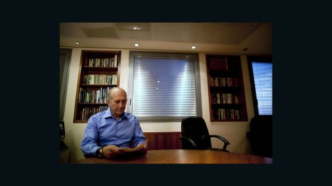 Former Israeli Prime Minister Ehud Olmert poses for photographers at his office in 2010.