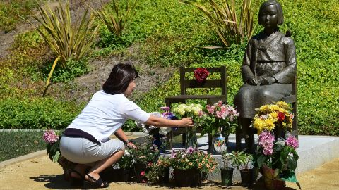 """A woman arranges flowers in front of a """"comfort woman"""" statue in Glendale, California."""