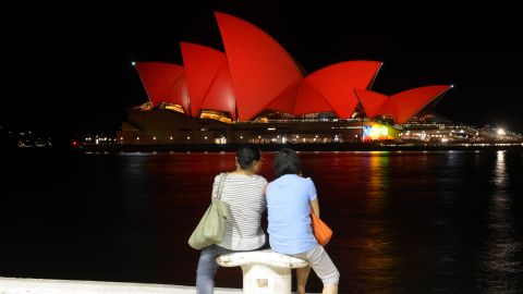 Chinese tourists view the Sydney Opera House which is lit up red to welcome in the Lunar New Year of the Monkey in Sydney on February 8, 2016.