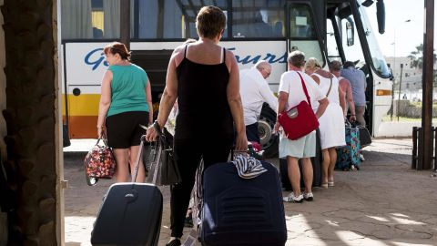 Tourists leave a hotel Wednesday in Banjul after a state of emergency went into effect.