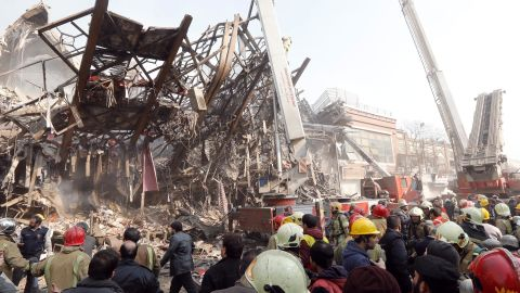 Authorities surround the debris of the collapsed building, which was one of Tehran's oldest high-rises.