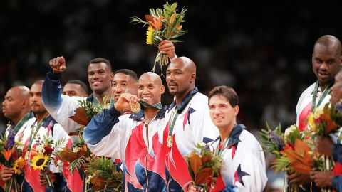"""The """"Dream Team's"""" Reggie Miller, center, flashes his gold medal surrounded by other members of the US men's basketball team during the medal presentation at the 1996 Summer Olympics. Standing, from left, are Charles Barkley, Grant Hill, Penny Hardaway, David Robinson, Scottie Pippen, Miller, Karl Malone, John Stockton and Shaquille O'Neal."""