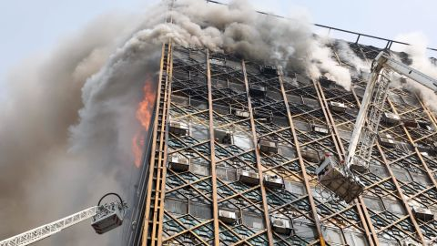 Firefighters work to control the blaze. Fars agency cited Mojtaba Doroodian, head of the shirt makers' union, as saying that the fire was the result of a leak in a small gas cylinder on the 10th floor, which caused an explosion when a merchant turned on the lights in his store. Tehran Fire Department spokesman Jalal Maleki said the cause of the building fire and collapse is being investigated.