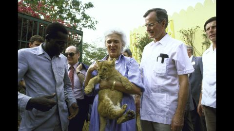 Bush holds a lion cub while she and her husband visit a garden project in 1985.
