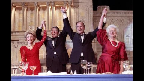 President Reagan and Vice President Bush, accompanied by their wives, join hands after Reagan endorsed Bush's run for the presidency during a dinner in Washington on May 11, 1988.