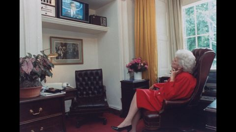 Bush watches her husband from a White House television as he speaks during a news conference.