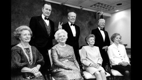 """President Bush gives his wife """"bunny ears"""" during an event at the Gerald R. Ford Library on April 16, 1997. Also pictured are former Presidents Ford and Jimmy Carter, as well as former first ladies Lady Bird Johnson, Betty Ford and Rosalynn Carter."""