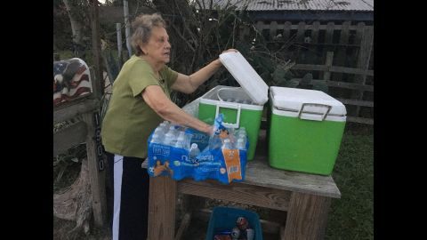 """Pamela Taylor, 88, has lived in Brownsville, Texas, since 1947. Taylor says she has had people from """"all over the world"""" arrive on her property, and she says she has even found them in her living room. Every night, she fills a cooler in front of her house with bottles of water for migrants who made the journey, Border Patrol officers, or anybody else who finds themselves near the front steps of her house."""
