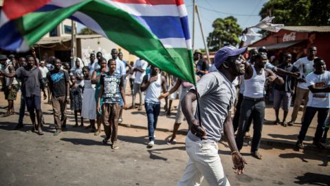 """A man waves a Gambian flag while he celebrates the victory of Gambia's opposition candidate Adama Barrow during the Presidential Elections on December 2, 2016, in Serekunda, Banjul. The impoverished west African nation of Gambia is set for a rare handover of power after long-serving President Yahya Jammeh suffered a shock defeat at the polls. Rights bodies and media watchdogs accuse Jammeh of cultivating a """"pervasive climate of fear"""" during his 22 years in office and of crushing dissent against his regime.  / AFP / MARCO LONGARI        (Photo credit should read MARCO LONGARI/AFP/Getty Images)"""