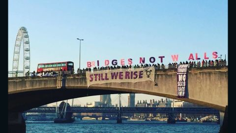 """Protesters hold letters spelling out """"Bridges Not Walls"""" on London's Waterloo Bridge on Friday morning."""