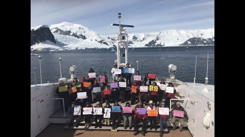 """Supporters in the Antarctic Peninsula take part in a women's march on Saturday, January 21. According to organizers, the march includes about 30 people who are eco-minded tourists and non-government scientists. Some held signs saying,  """"Penguins for Peace"""" and """"Seals for Science."""""""