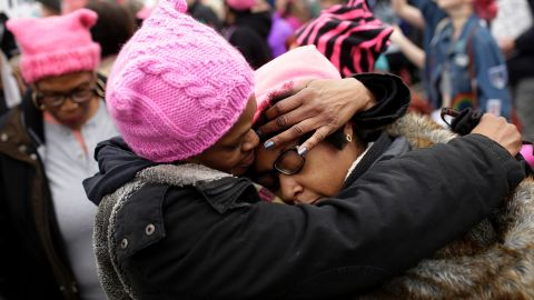 A mother embraces her daughter during the Women's March on January 21, 2017 in Washington, DC. Hundreds of thousands of people flooded US cities Saturday in a day of women's rights protests to mark President Donald Trump's first full day in office.