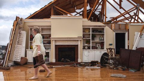 Jenny Bullard carries a pair of boots from her storm-damaged home in Adel on January 22.