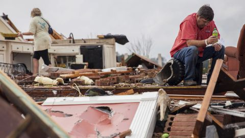 Jeff Bullard sits in what used to be the foyer of his home as his daughter, Jenny, looks through debris in Adel on January 22. Gov. Nathan Deal declared a state of emergency in several counties.
