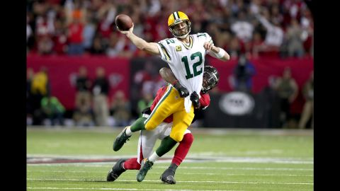 Packers quarterback Aaron Rodgers throws as he is hit by Falcons linebacker Deion Jones in the first quarter.