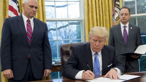 President Donald Trump signs an executive order withdrawing the US from the Trans-Pacific Partnership alongside US Vice President Mike Pence and White House Chief of Staff Reince Priebus in the Oval Office of the White House in Washington, DC, January 23, 2017.
