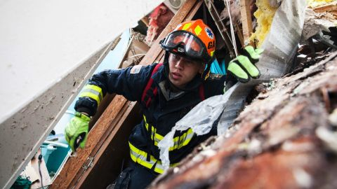 A rescue worker searches inside a mobile home in Albany on January 23.