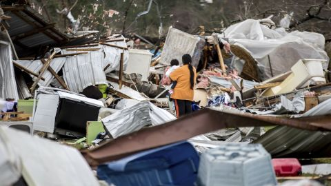 A woman holds a child while walking through a tornado-damaged farm in Adel, Georgia, on Sunday, January 22.