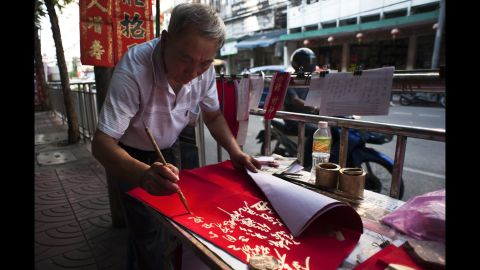 A calligrapher writes out New Year's greetings in Bangkok, Thailand, on Saturday, January 21.