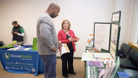 Cancer screening nurse navigator Charlene Marinelli (right), with the Graham Cancer Center, talks about colorectal cancer with an unnamed participant at an event geared toward men of color.