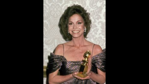 """Moore holds up the Golden Globe Award she won for """"Ordinary People."""""""