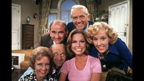 """Moore, in the pink shirt, poses with cast members of """"The Mary Tyler Moore Show"""" in 1974. Clockwise from Moore are Gavin MacLeod, Betty White, Ed Asner, Ted Knight and Georgia Engel. The show ended in 1977 but spurred several spinoffs, including """"Rhoda"""" and """"The Lou Grant Show."""""""