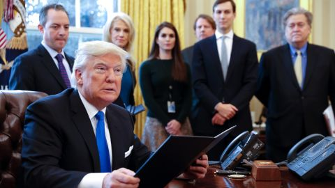 President Donald Trump signs an executive order on the oil pipeline industry while senior aides look on.