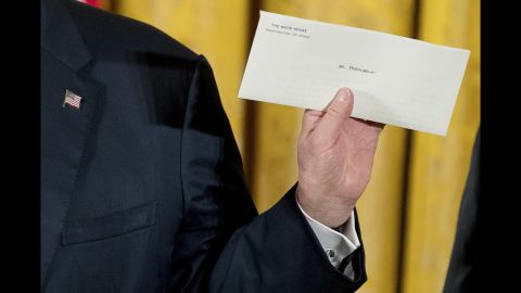 Trump holds up a letter Sunday, January 22, that was left for him by former President Barack Obama.