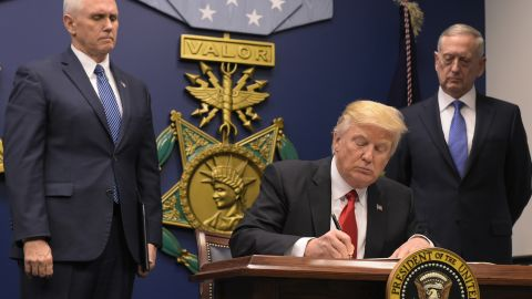 """US President Donald Trump signs an executive order alongside US Defense Secretary James Mattis and US Vice President Muike Pence on January 27, 2016 at the Pentagon in Washington, DC.Trump signed an order Friday to begin what he called a """"great rebuilding"""" of the US armed services, promising new aircraft, naval ships and more resources for the military. """"Our military strength will be questioned by no one, but neither will our dedication to peace. We do want peace,"""" Trump said in a ceremony at the Pentagon. / AFP / MANDEL NGAN        (Photo credit should read MANDEL NGAN/AFP/Getty Images)"""